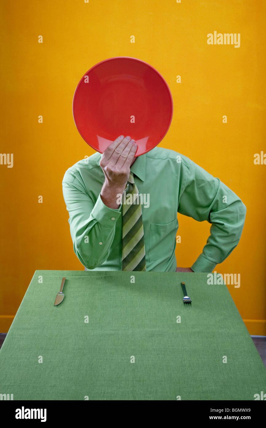 Mann hält rot Speiseteller über Gesicht beim Sitzen am grünen Tisch. Stockbild