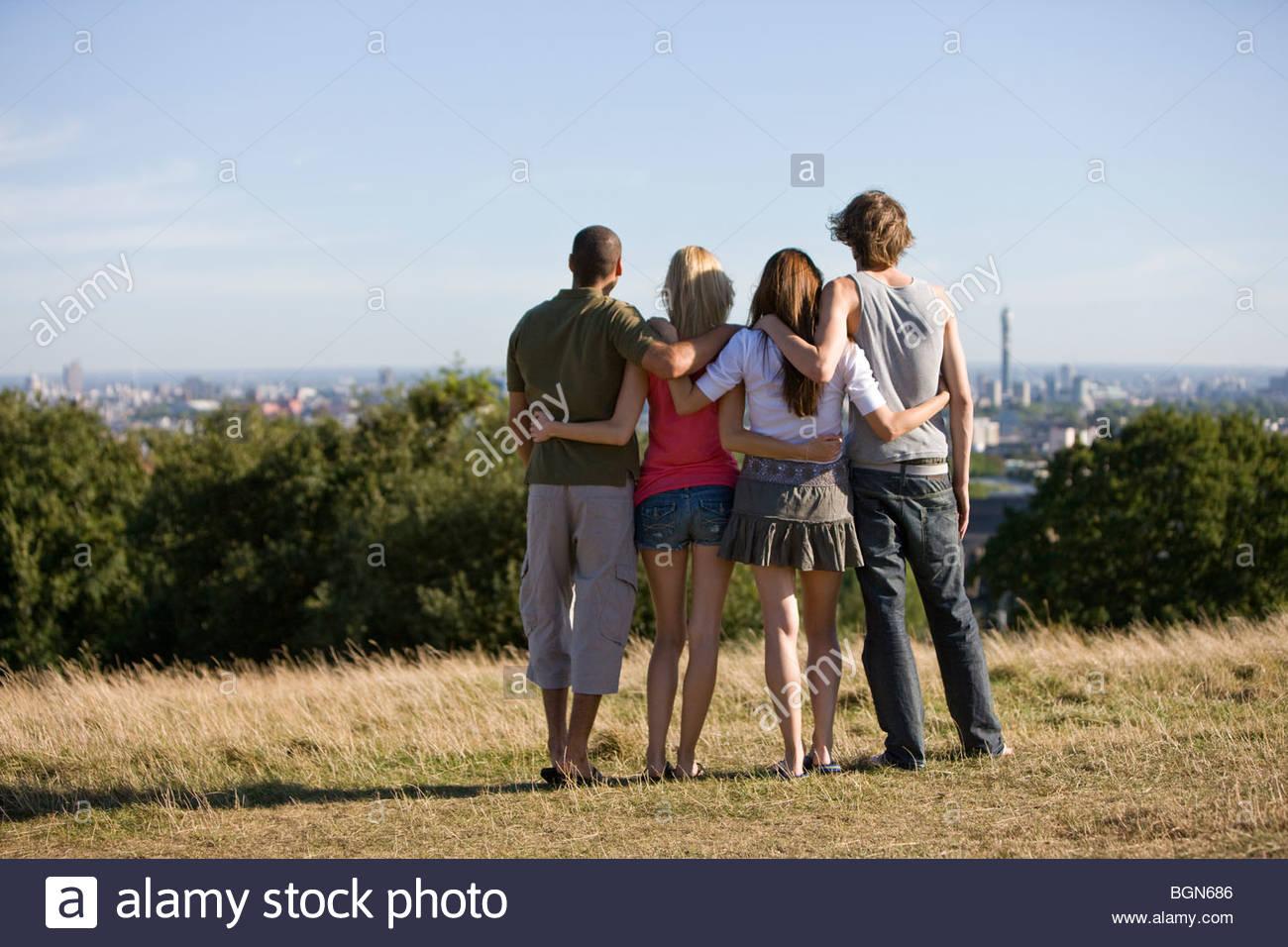 Vier Freunde in einem Park, Blick über die Stadt, Rückansicht Stockbild