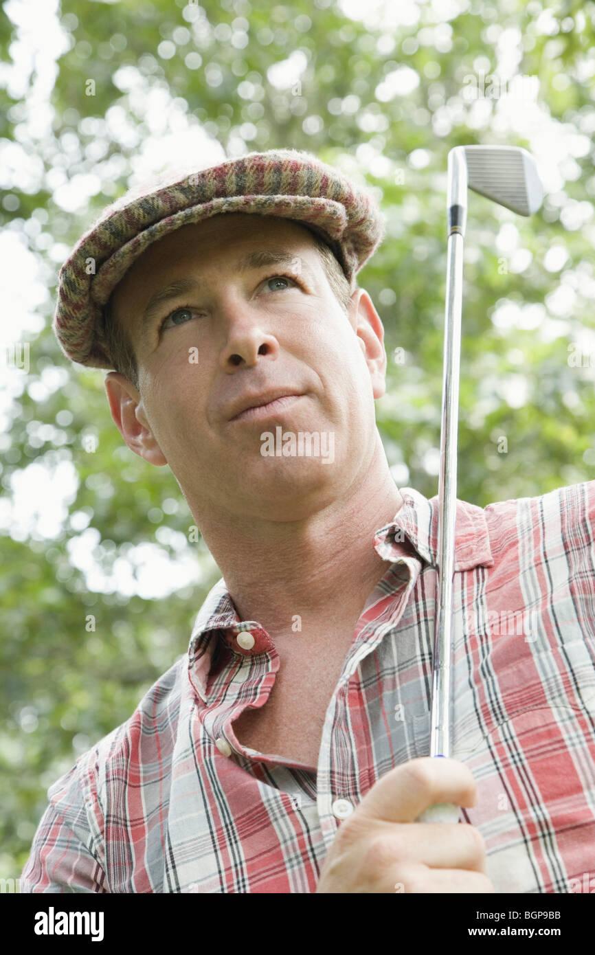 Nahaufnahme von einem reifen Mann hält einen Golfschläger Stockbild