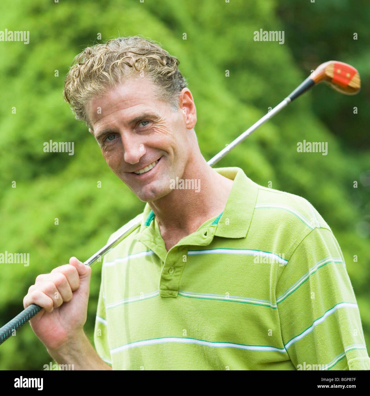 Porträt von einem reifen Mann hält einen Golfschläger und lächelnd Stockbild
