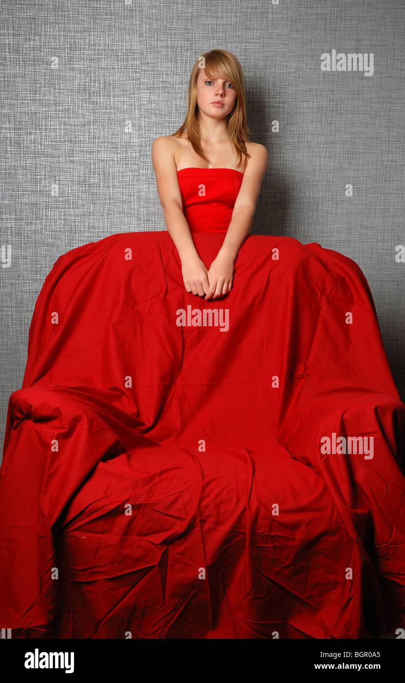 Jugend-Frau in rot und große Sessel Stockbild