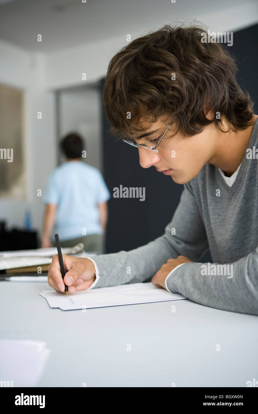 College-Student schreiben am Schreibtisch im Klassenzimmer Stockbild
