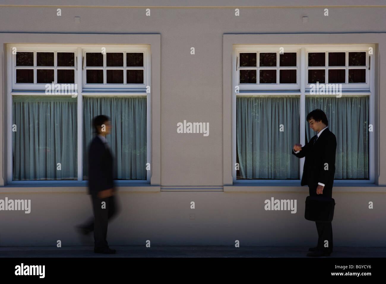 Junger Geschäftsmann auf Bürgersteig stehen, zeitgleich mit einem anderen Mann Ansätze prüfen Stockbild