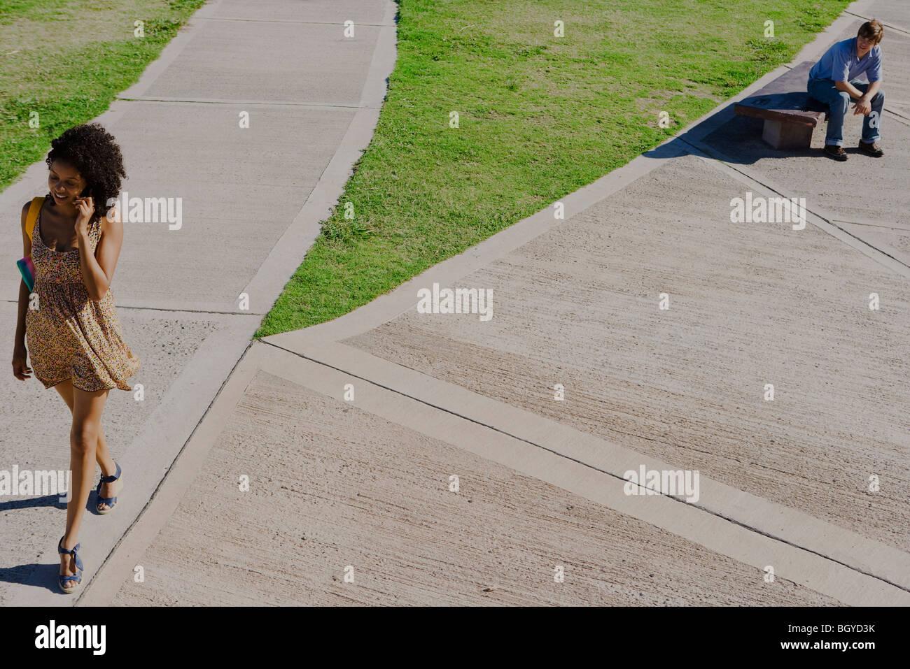 Attraktive junge Frau zu Fuß in Park, reden über Handy, jungen Mann beobachtete sie von nahe gelegenen Stockbild