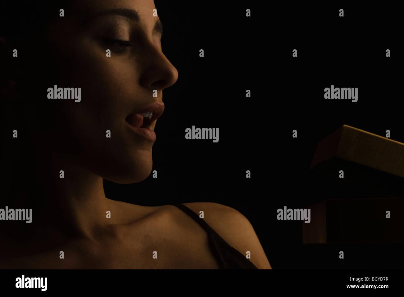 Frau, die Lippen lecken, wie sie kleine Geschenk-Box öffnet Stockbild