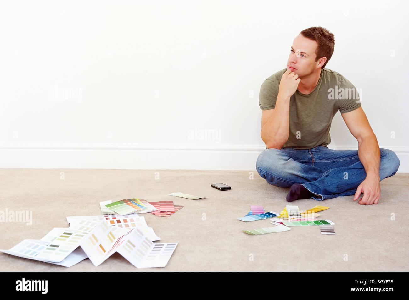Mann sitzt im Stock mit Farbmuster Stockbild