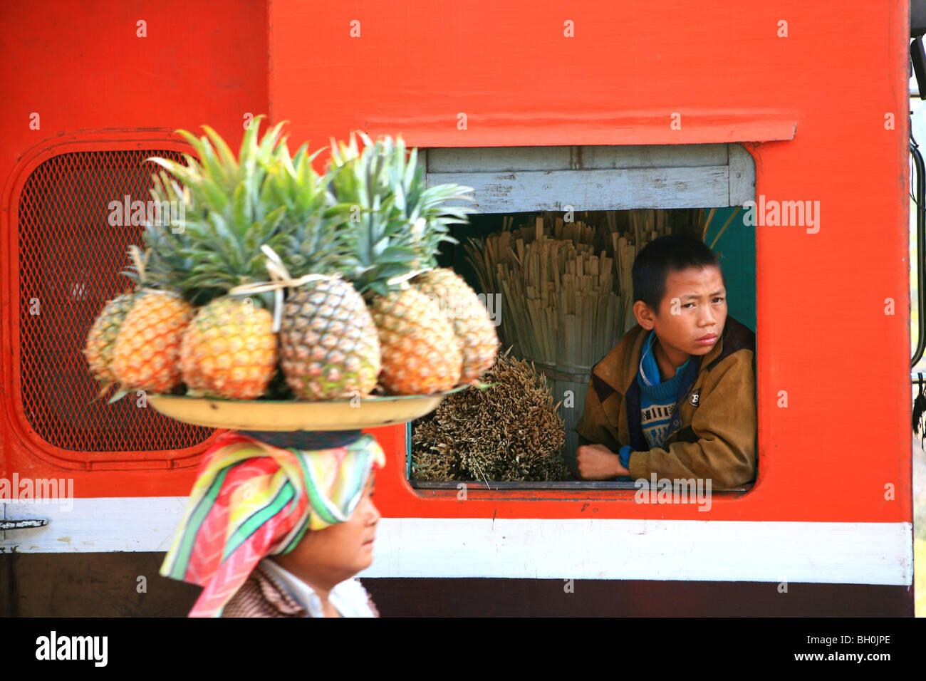 Eine Frau verkauft Frucht, ein Junge aus dem Fenster eines Zuges, Hispaw, Shan State in Myanmar, Myanmar, Asien Stockfoto