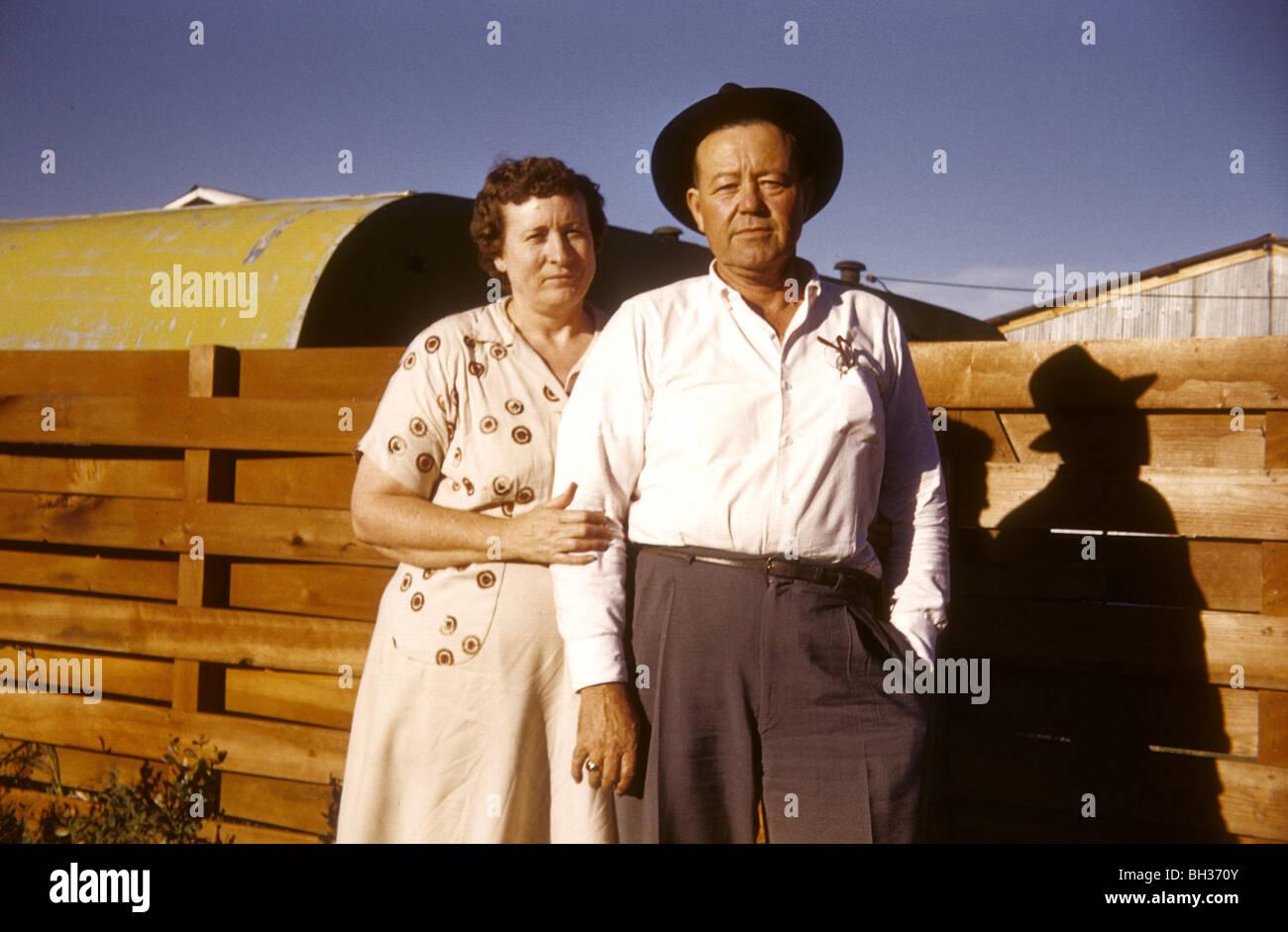 Alt verheiratet paar stehen durch einen Zaun im amerikanischen Westen während der 1950er und 1960er Jahren. Stockbild