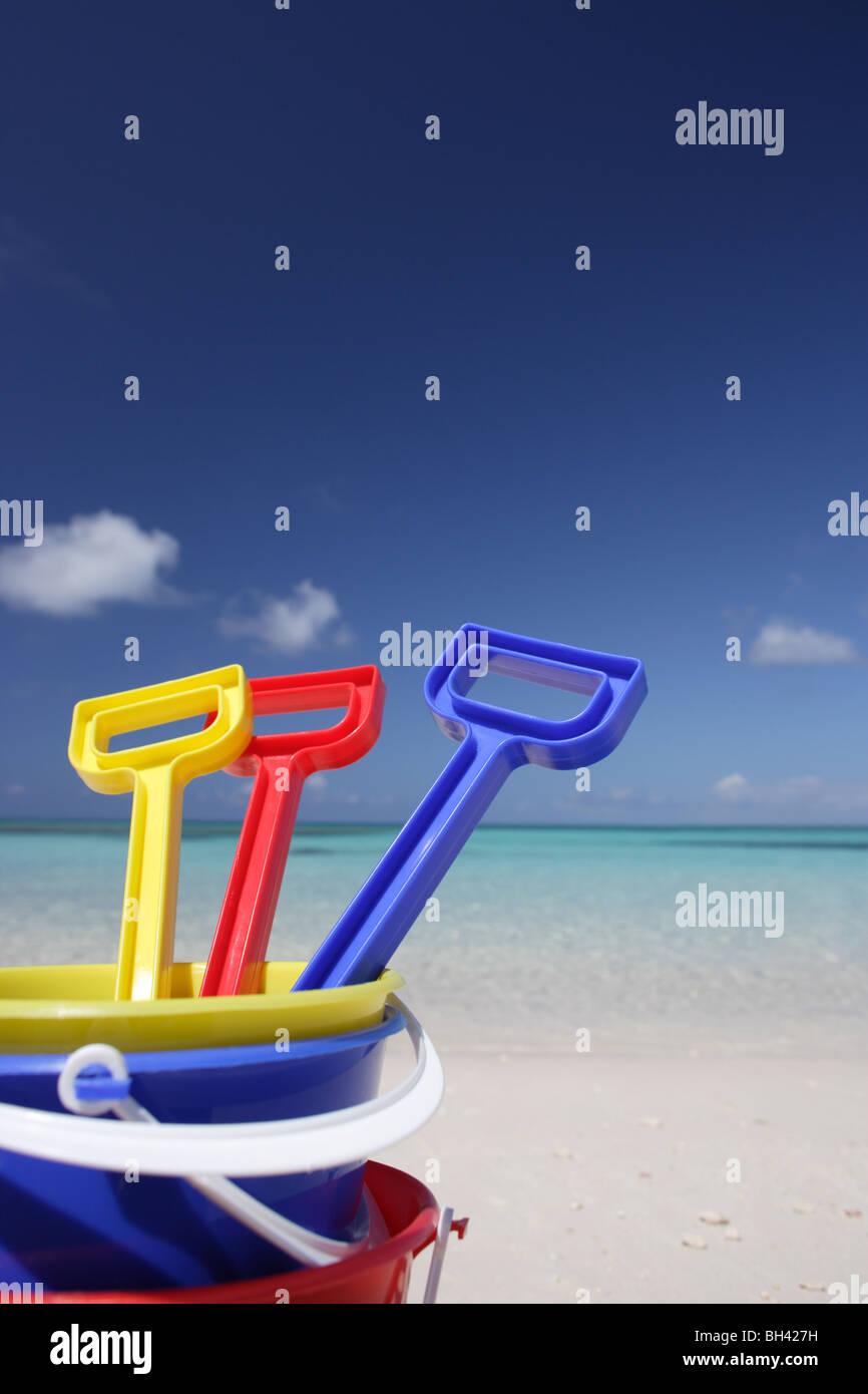 Drei Kinder Spielzeug Eimer und Spaten auf einem einsamen tropischen Strand Stockbild