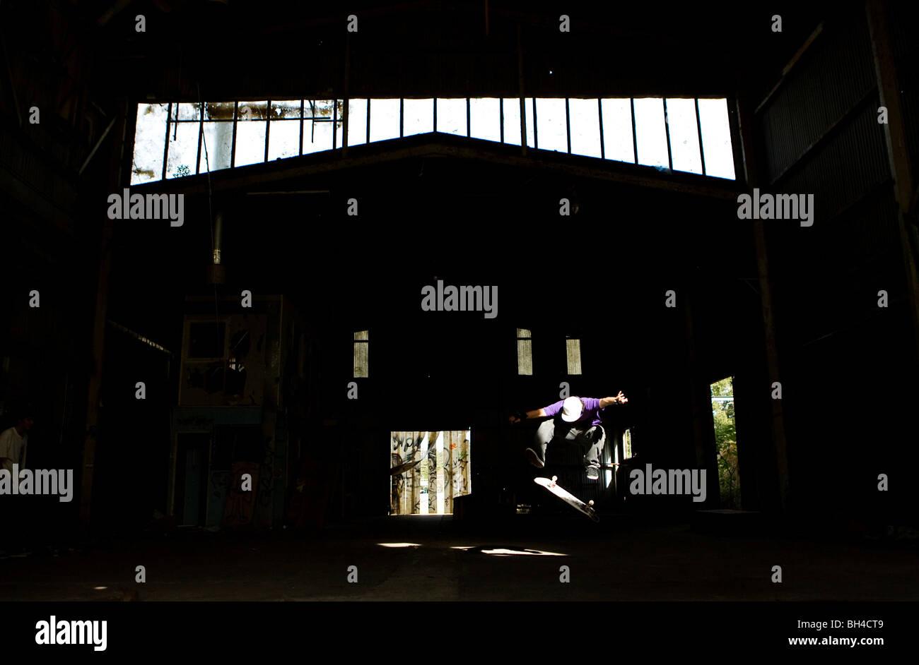 Eine Skater führt einen Kick Flip in einem verlassenen Lagerhaus an der Central Coast, New-South.Wales, Australien. Stockbild