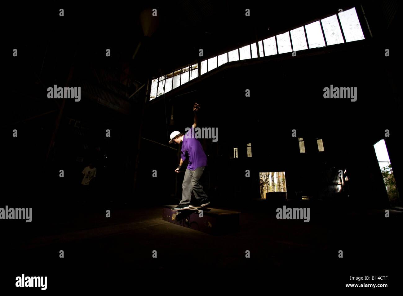 Eine Skater führt ein Smith Grind in einem verlassenen Lagerhaus an der Central Coast, New-South.Wales, Australien. Stockbild
