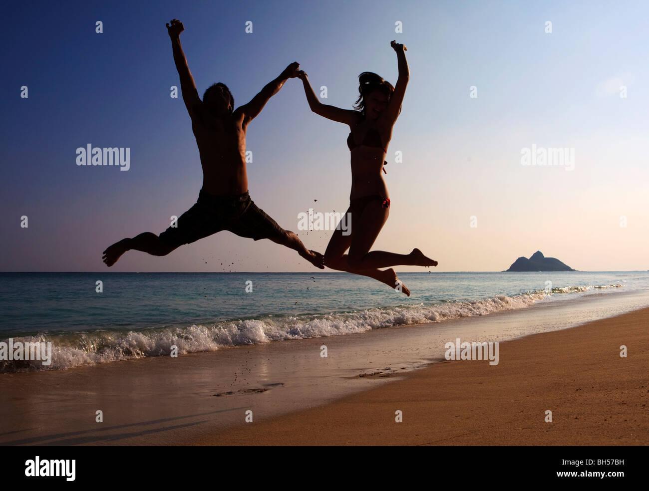 Silhouette eines Paares springen in der Luft am Strand von hawaii Stockbild