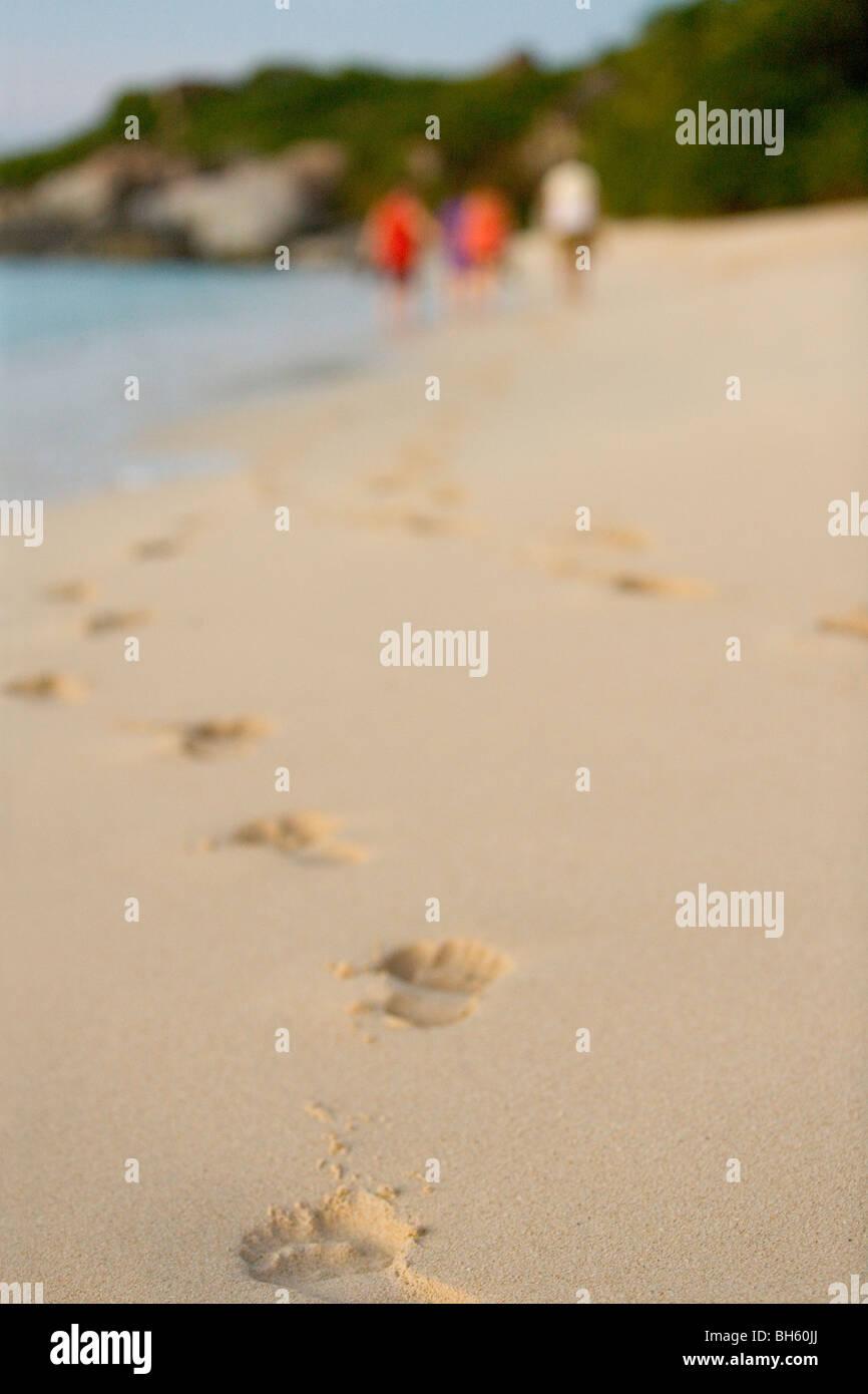Fußabdrücke auf einer tropischen Karibik-Strand und Touristen im Hintergrund. Stockbild