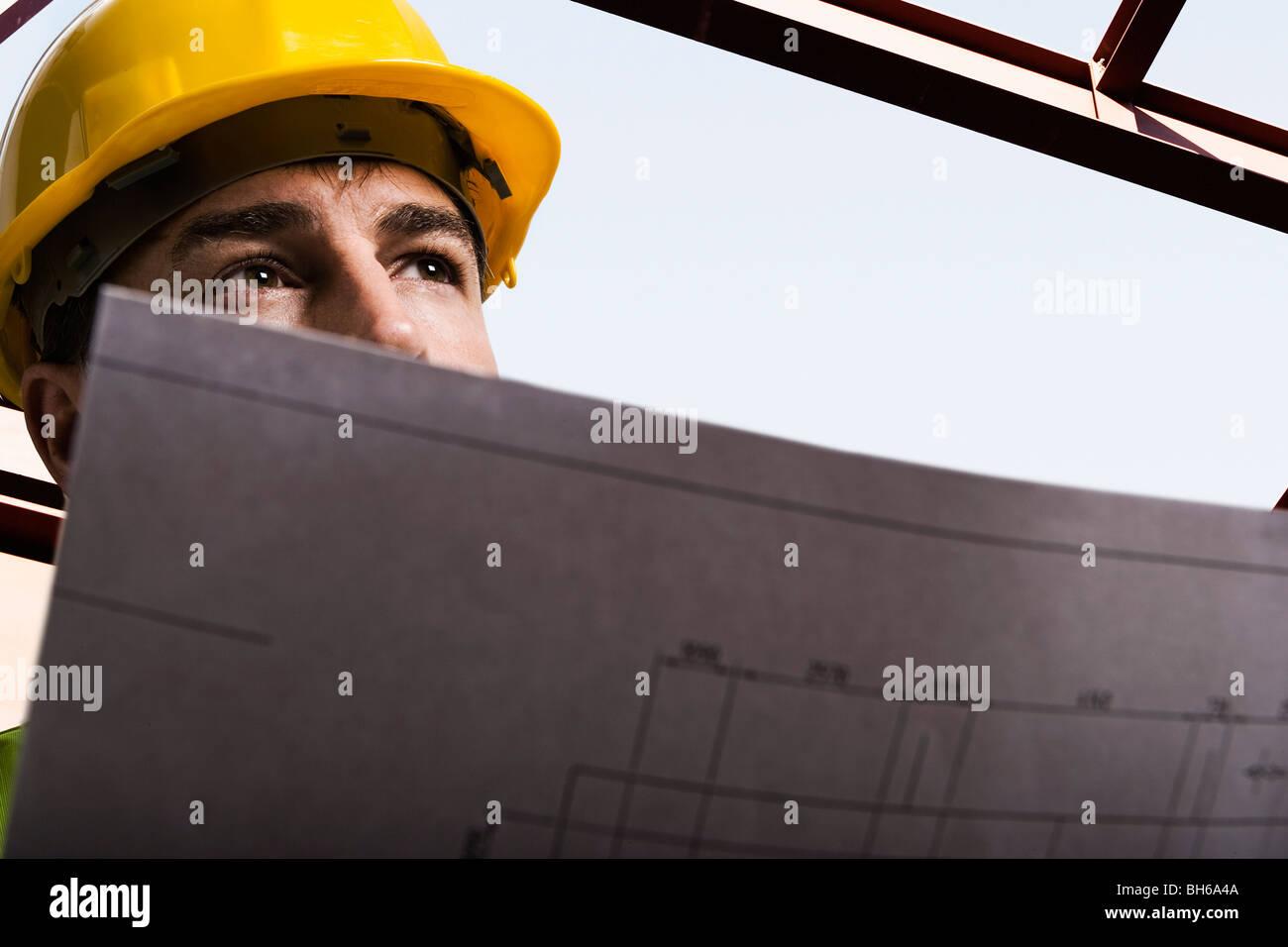 Arbeiter halten Konstruktionszeichnungen Stockbild