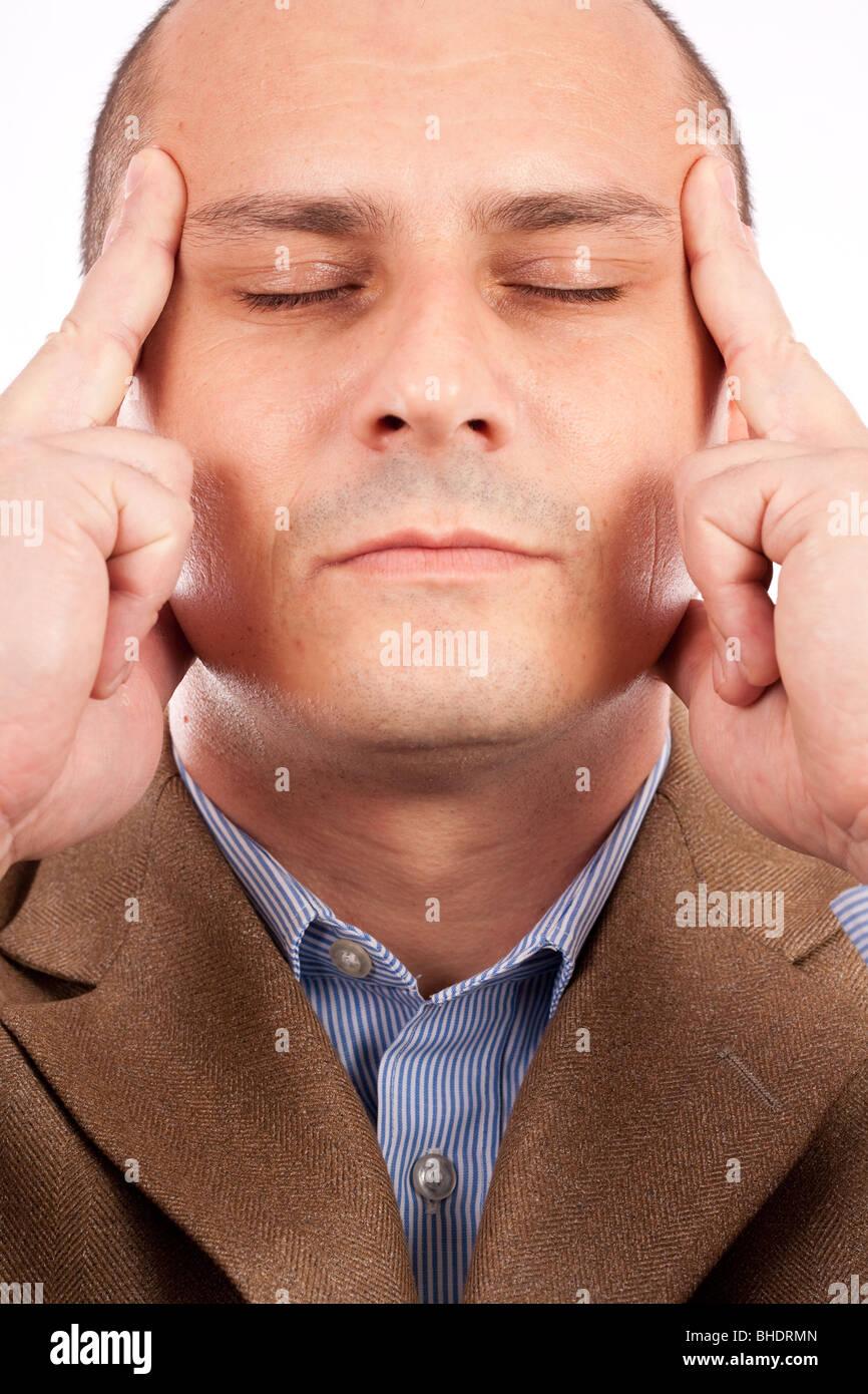 Junger Geschäftsmann mit geschlossenen Augen und eine Konzentration Ausdruck, isoliert auf weißem Hintergrund Stockbild