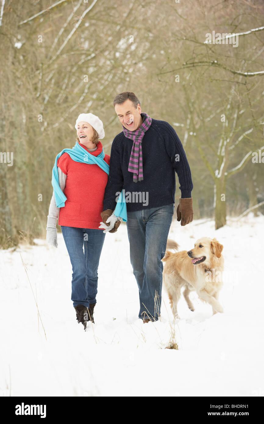 Älteres paar Walking Hund durch den verschneiten Wald Stockfoto