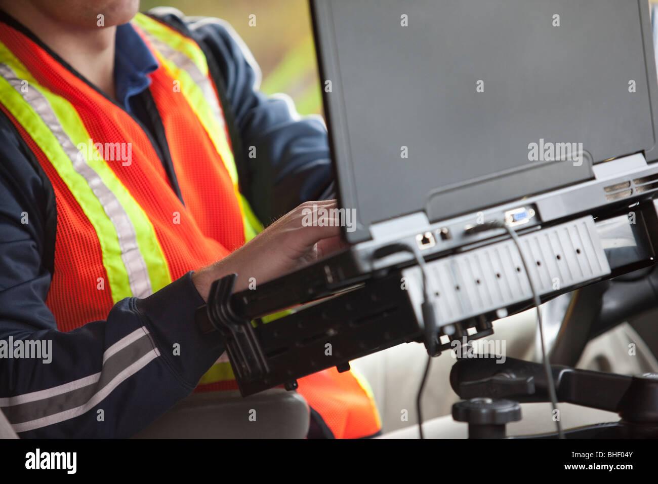 Inspektor mit einem Laptop in einem Fahrzeug Stockbild