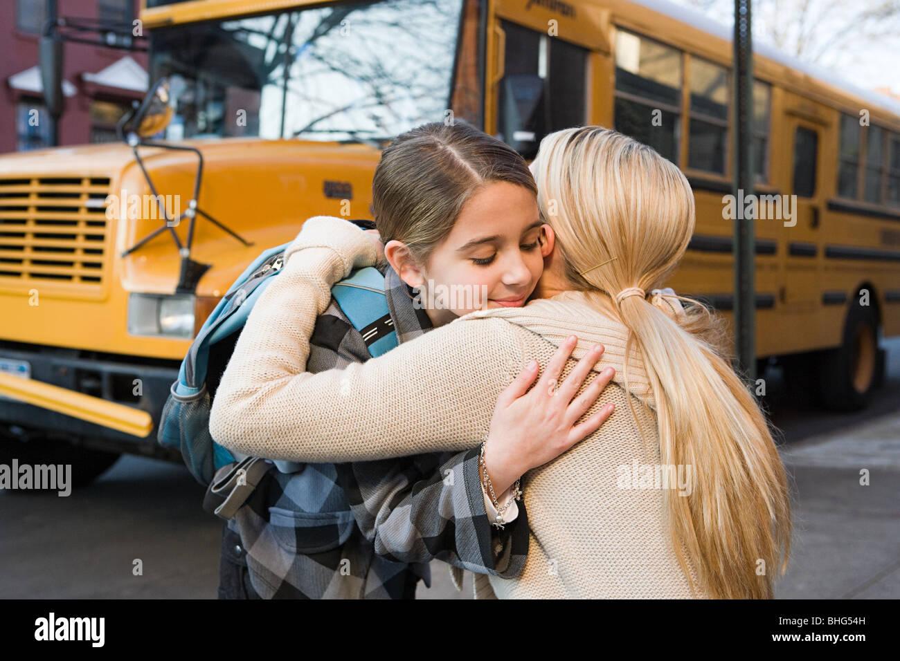 Mädchen und Mutter umarmt von Schulbus Stockbild