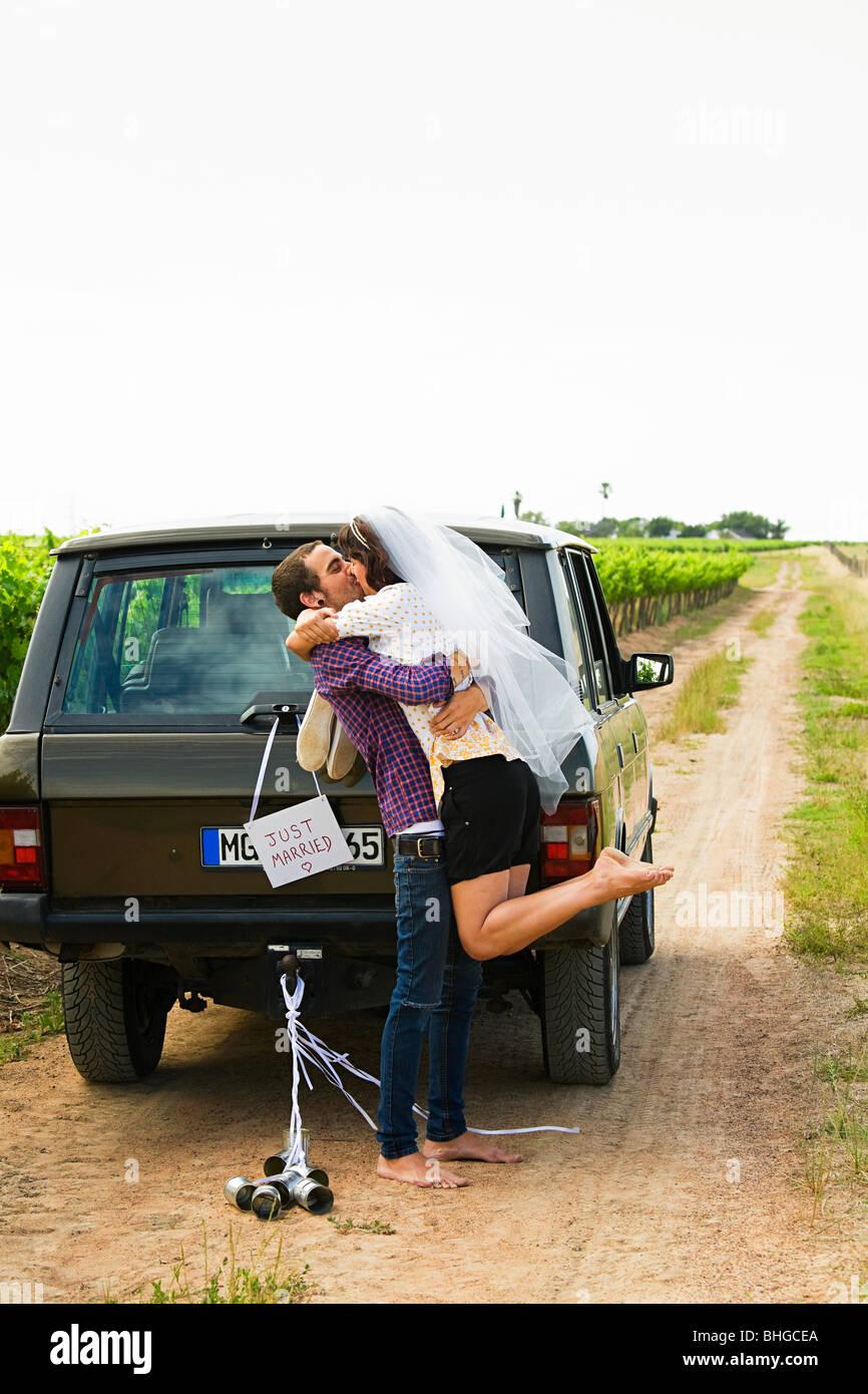 Brautpaar küssen mit einem Fahrzeug Stockbild