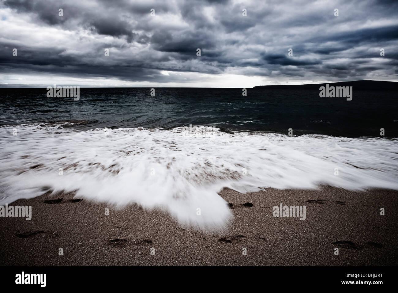 Wellen am Strand mit Fußspuren Stockbild