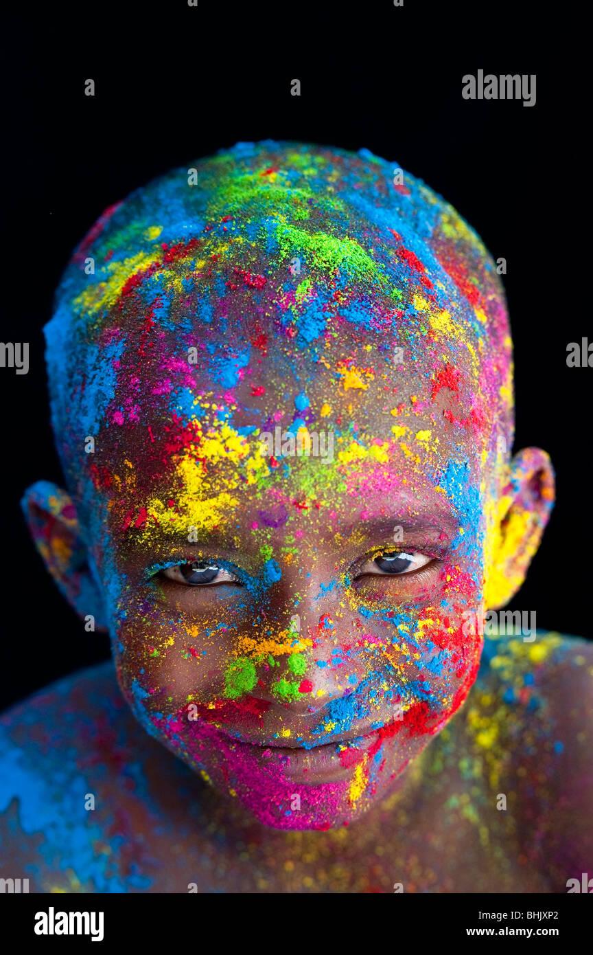 Glücklichen jungen bedeckt Farbpulver Pigment vor schwarzem Hintergrund Stockbild