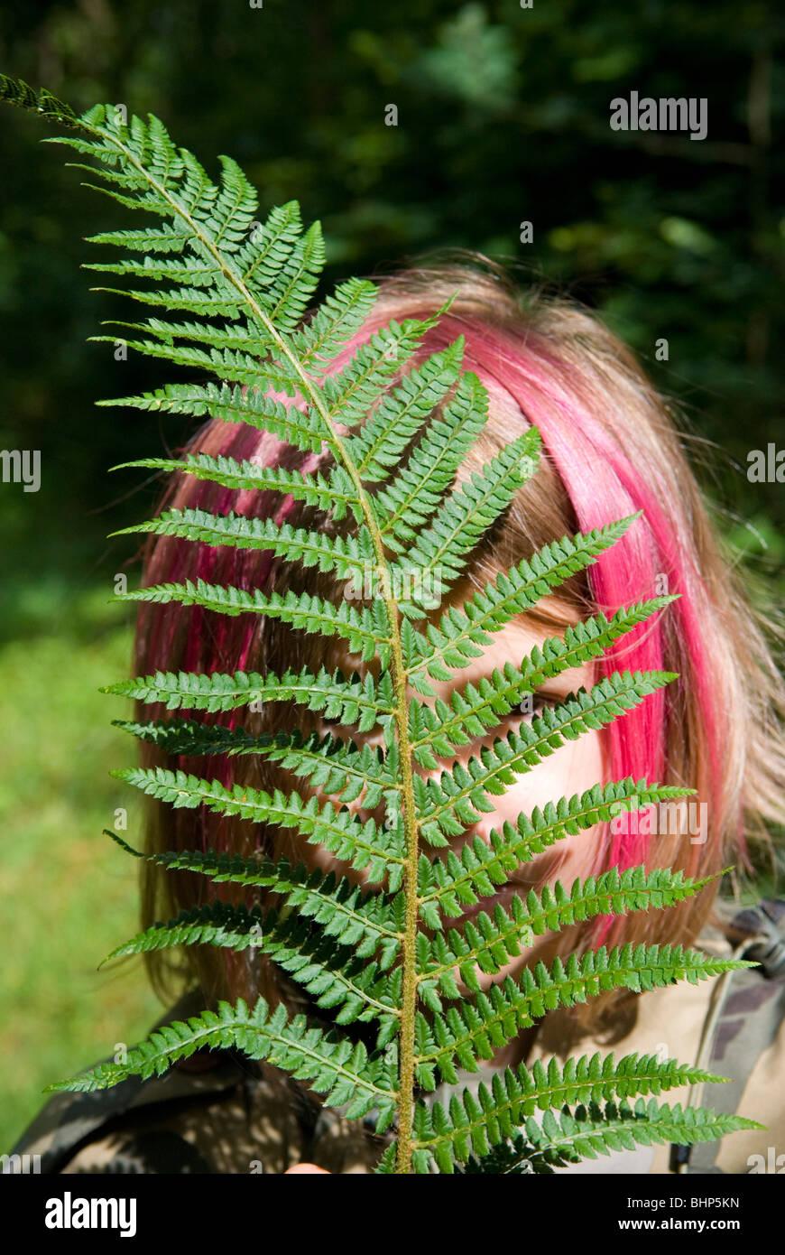 ein junges Mädchen mit rosa gefärbten Haaren in Bob verbirgt sich hinter einer leuchtend grünen Farn Stockbild
