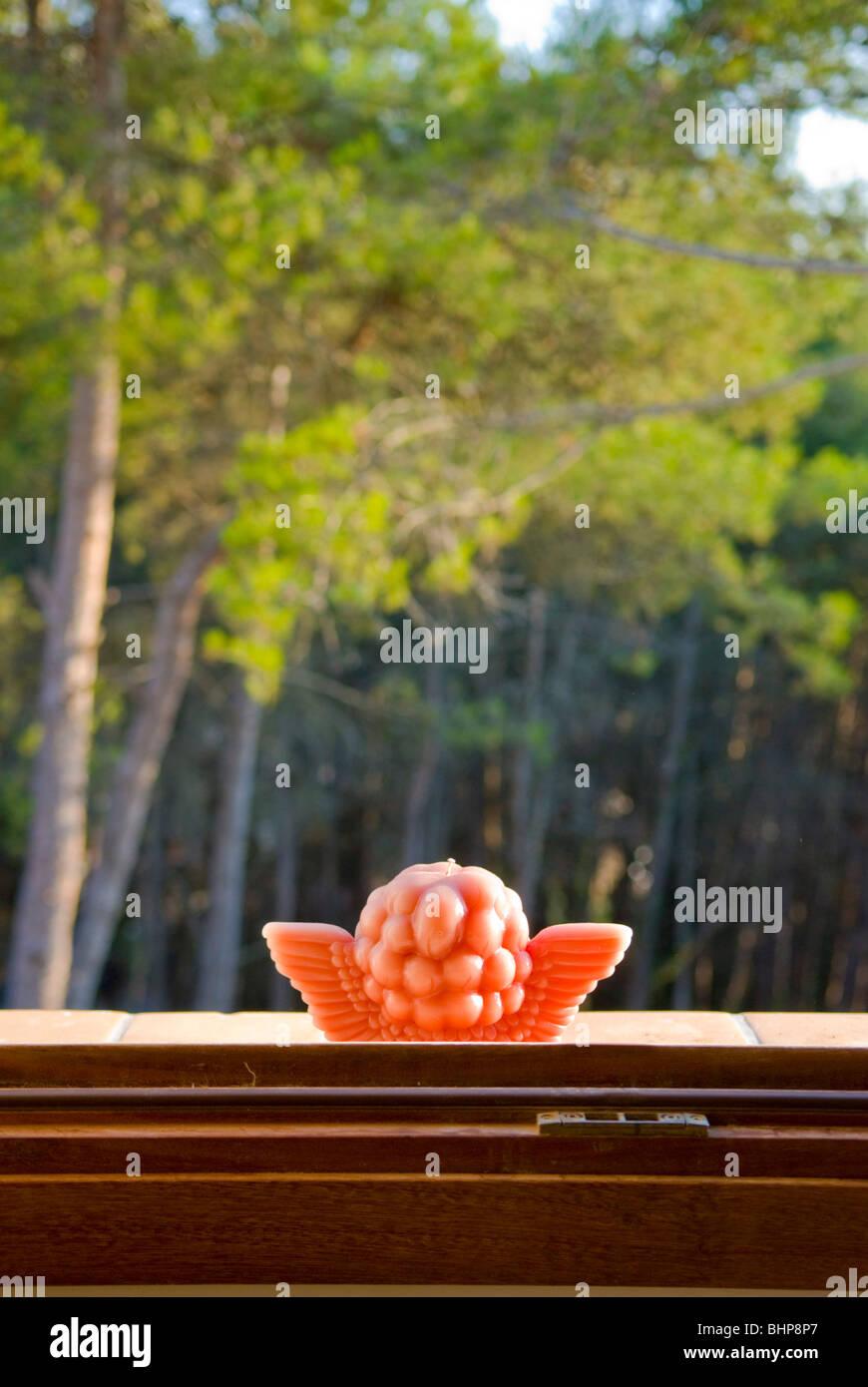 eine enge auf der Rückseite des roten Amor Kerze auf einem Fensterbrett in der Sonne mit Wald im Hintergrund Stockbild