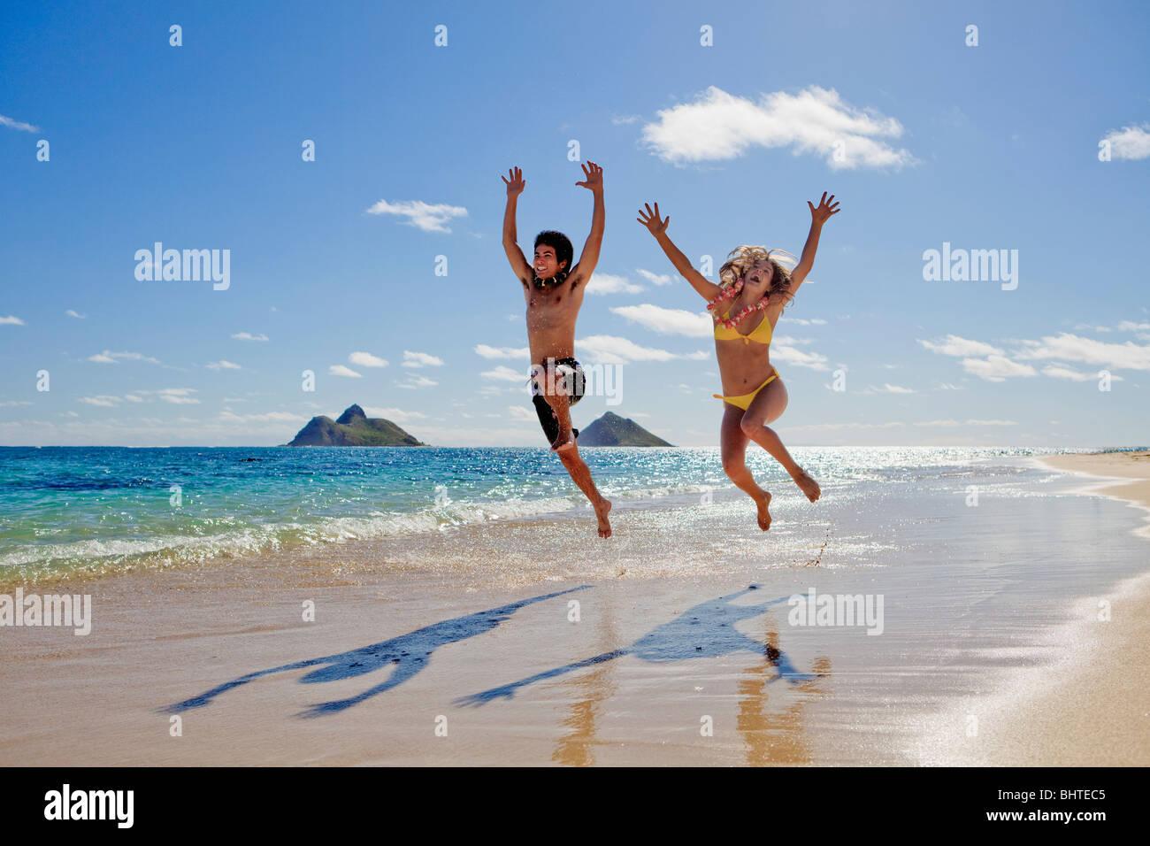 junges Paar springen vor Freude am Strand von hawaii Stockbild