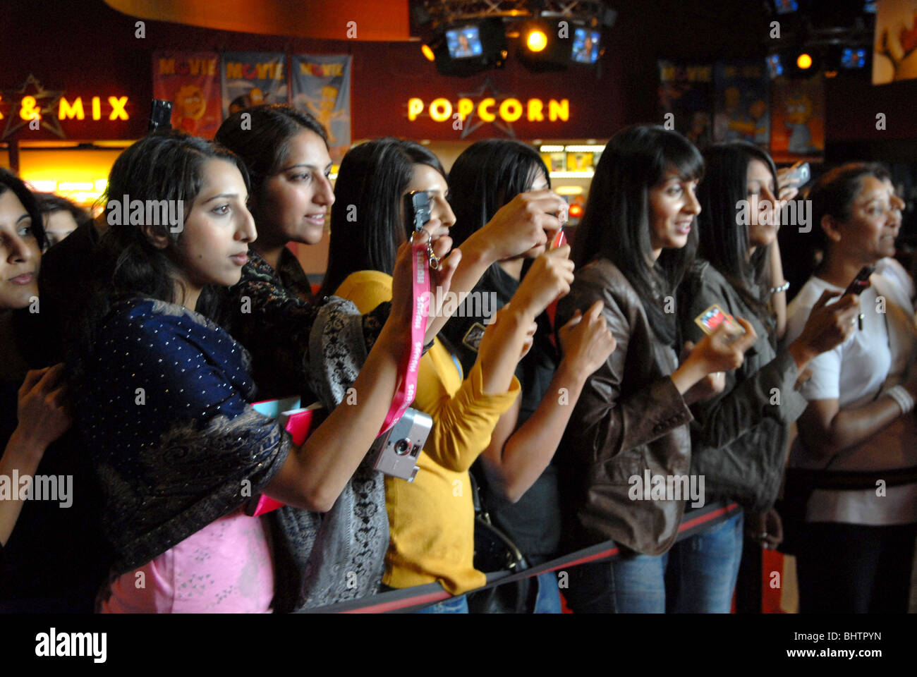 Einheimischen Briten geboren indische Frauen warten auf Bollywood-Stars bei der Kinowelt in Bradford, Yorkshire Stockbild