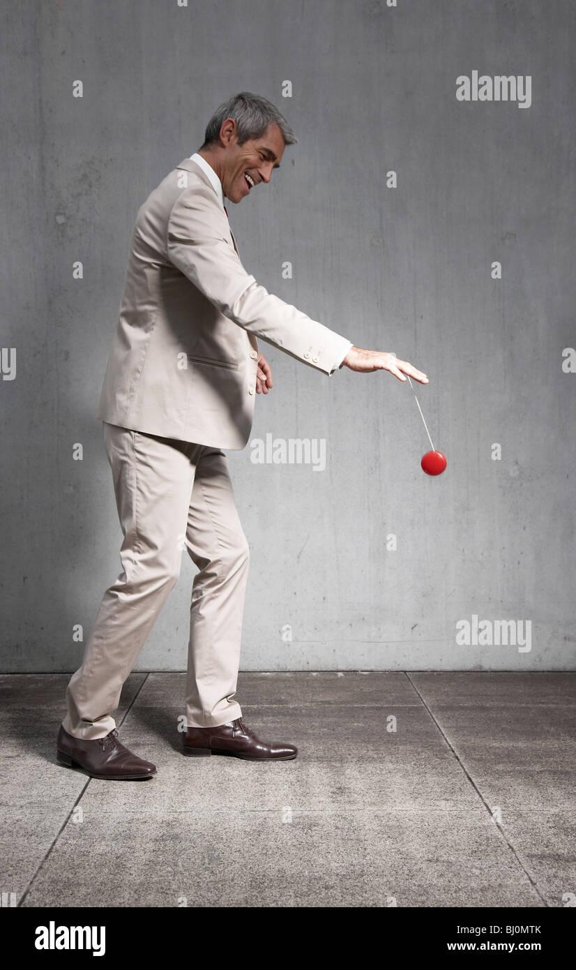 Geschäftsmann mit roten Yoyo spielen Stockbild