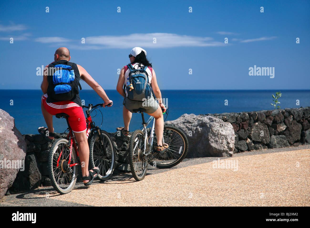 Touristen, die auf Fahrrädern mit Blick auf das Meer, Lanzarote, Kanarische Inseln, Spanien Stockbild