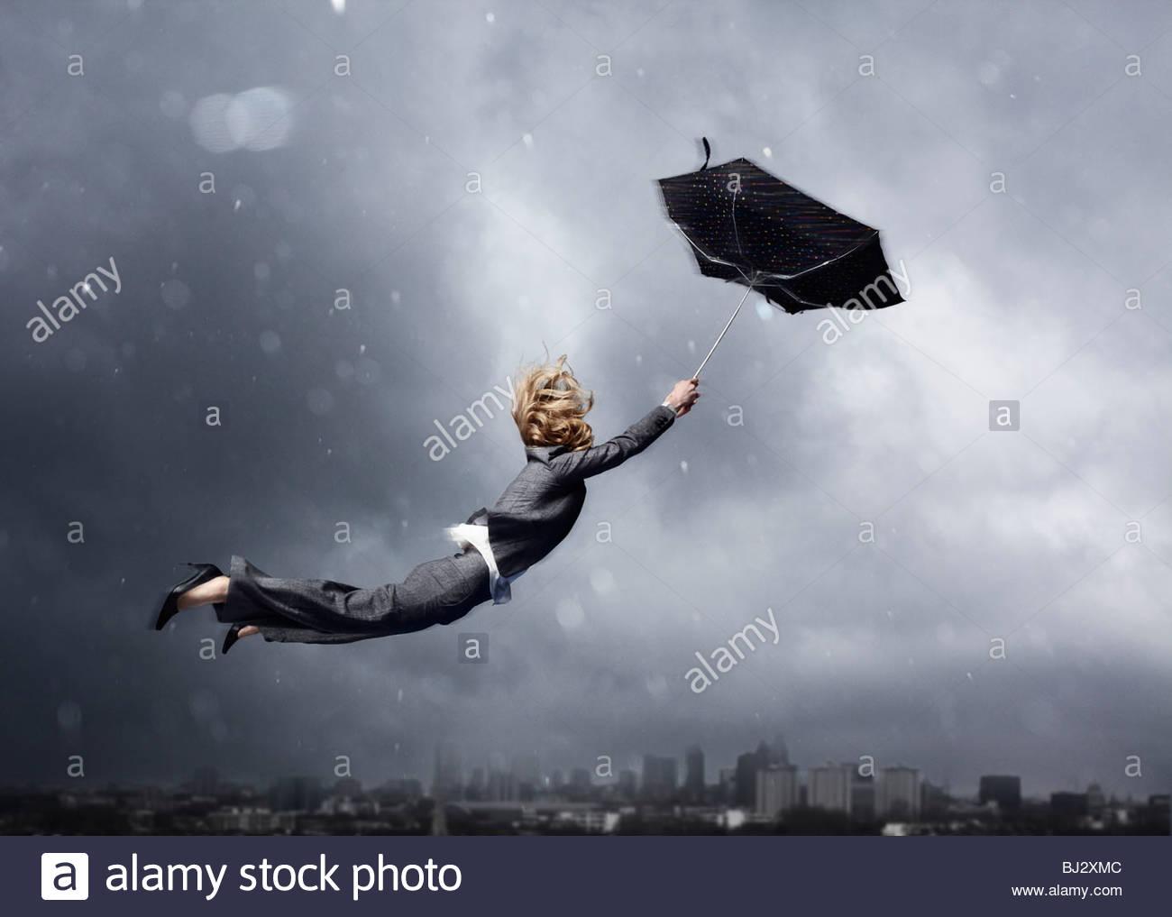 Frau wird von einem Regenschirm geblasen Stockfoto
