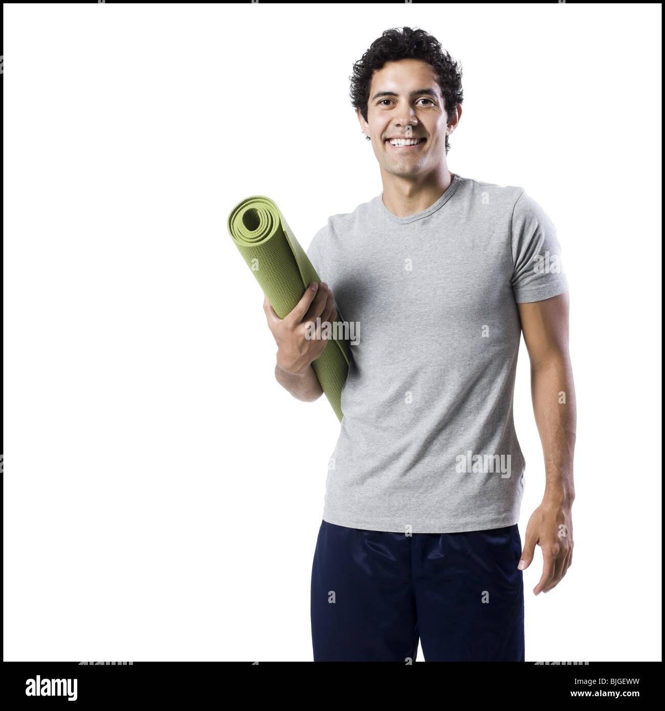 Mann hält eine Yoga-Matte Stockbild