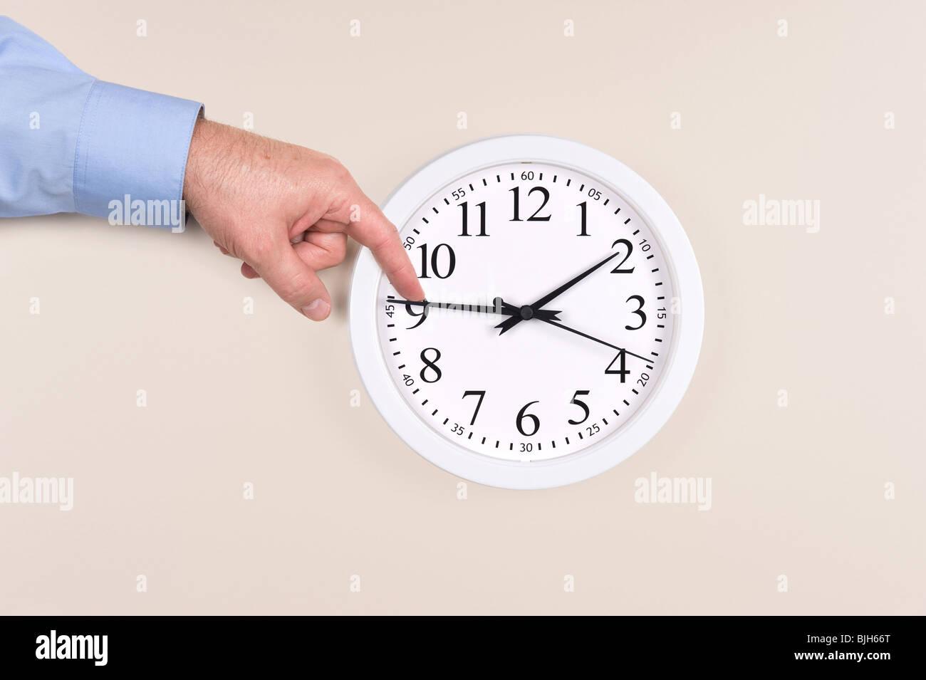 Ein Mann nutzt seine Finger, die Zeit auf einer Uhr auf Sommerzeit zurückzudrängen Stockbild