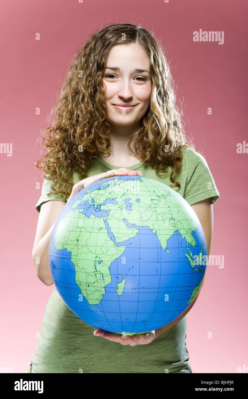 Frau hält einen Globus Stockbild