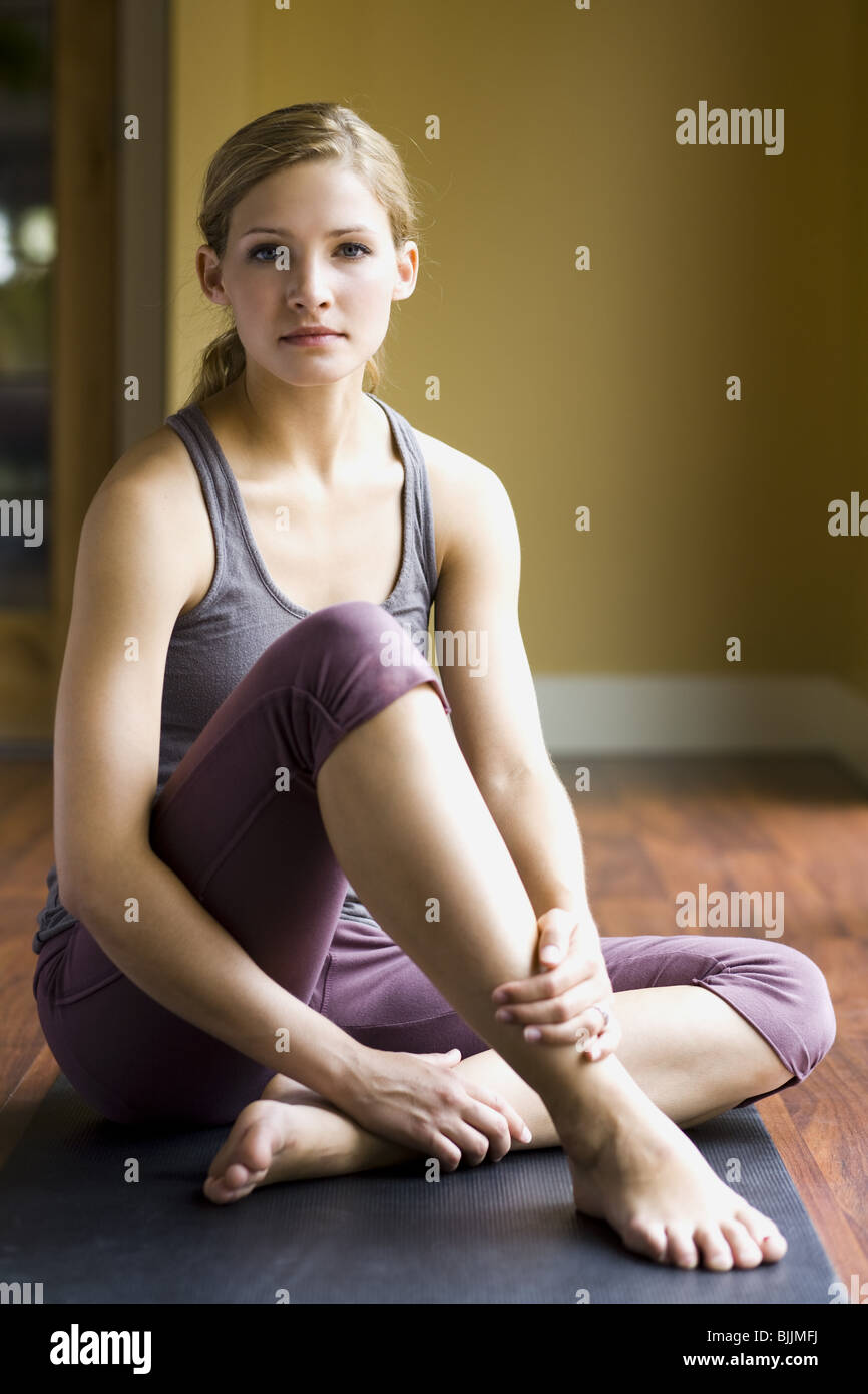 Frau sitzt auf Yoga matte Lächeln Stockbild