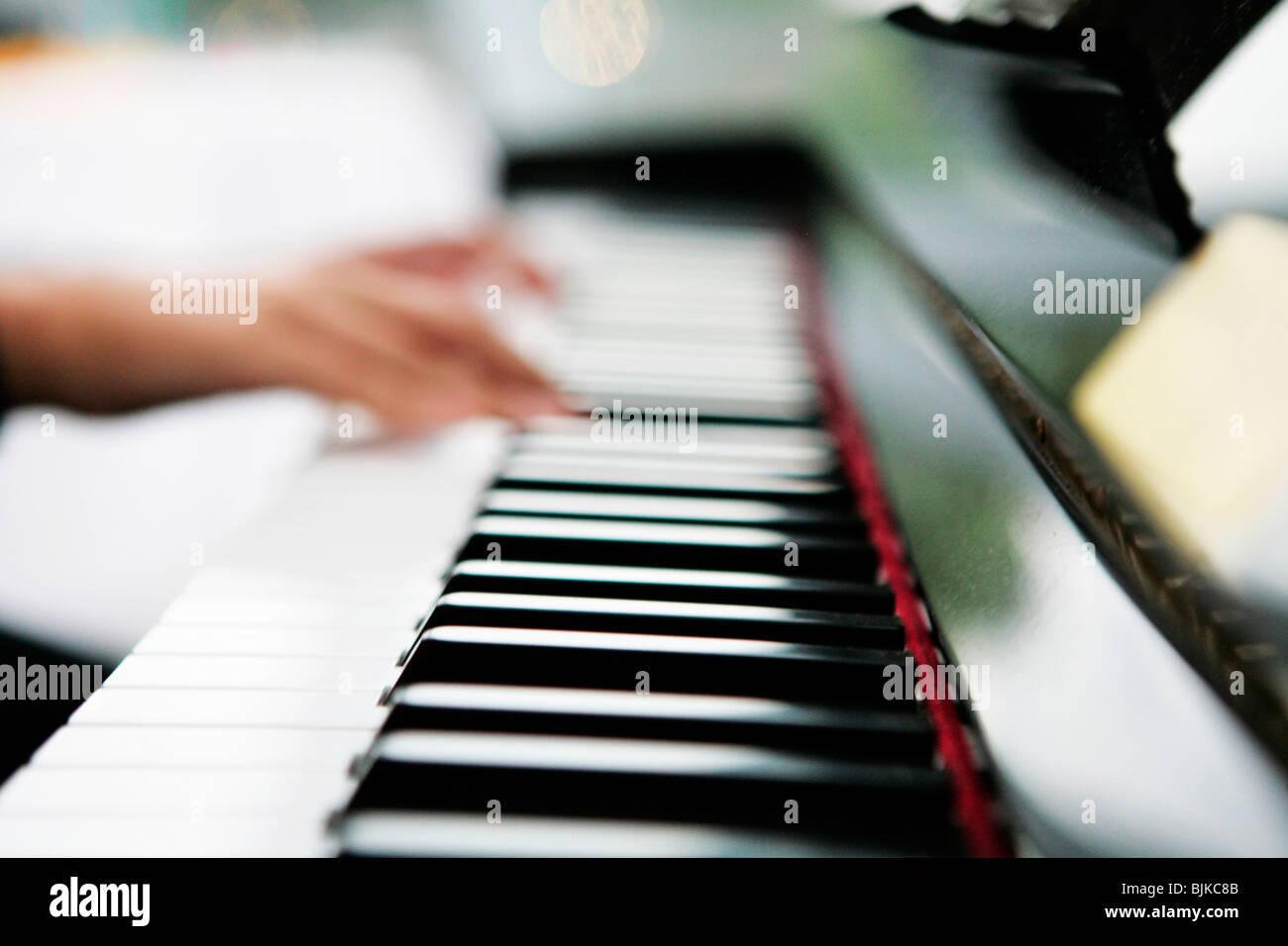 Hände auf einer Klaviertastatur Stockbild