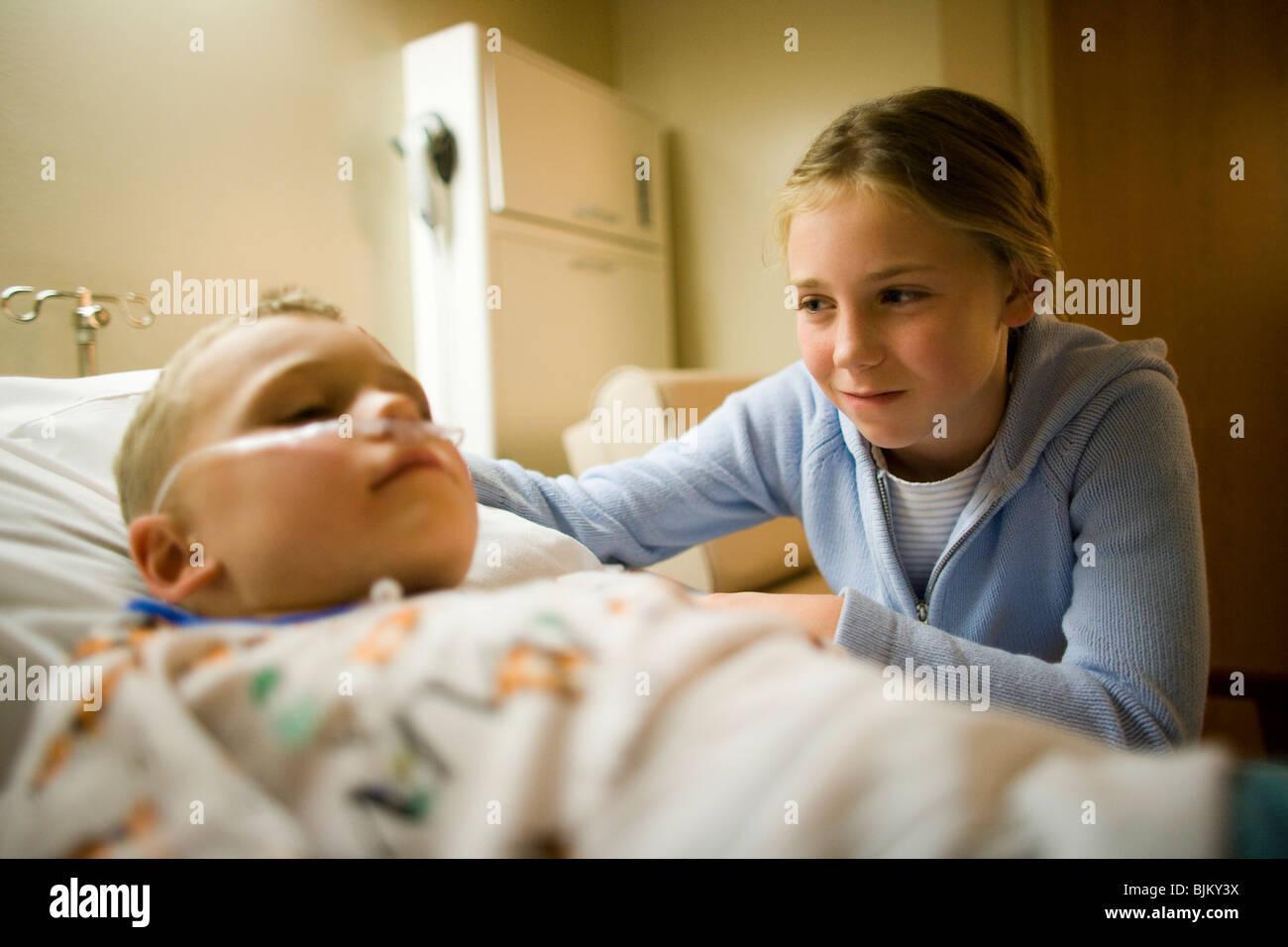 Junge Mädchen von Bruder im Krankenhausbett sitzen Stockbild