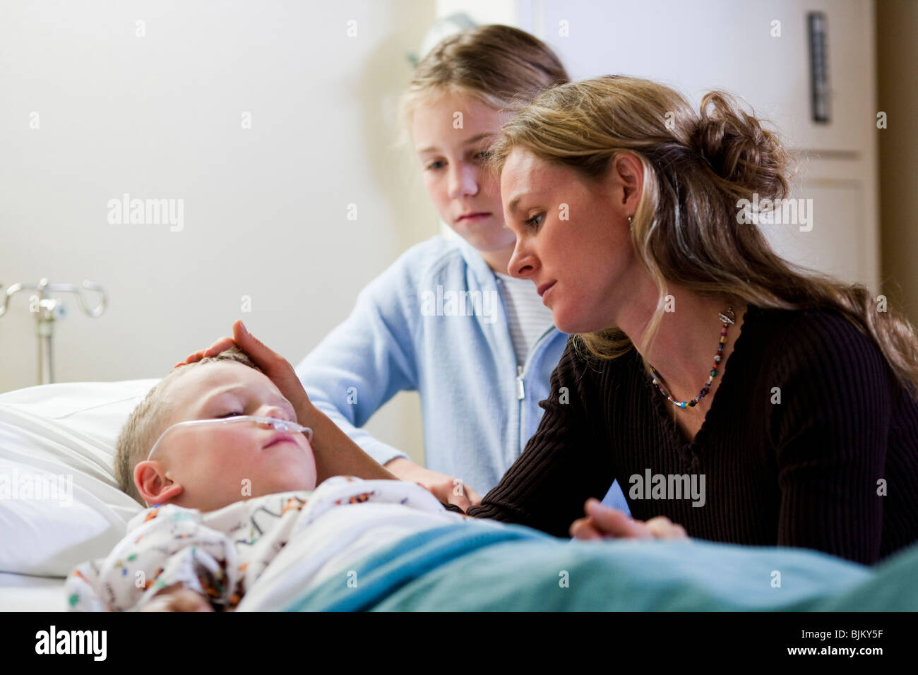 Mutter und Tochter sitzen junge Krankenhausbett Stockbild