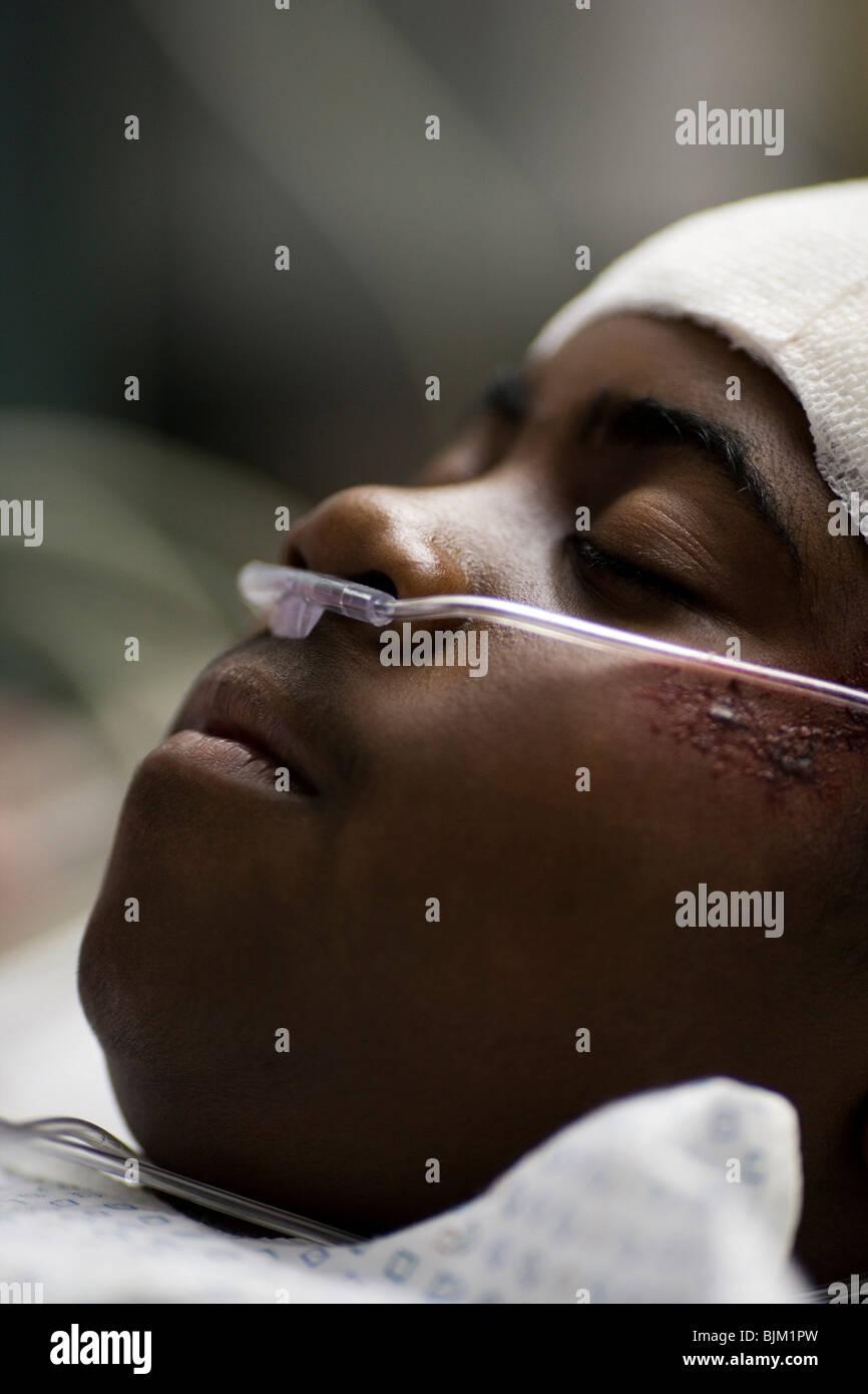 Junge im Krankenhausbett mit Kopf Bandagen mit Vater an seiner Seite Stockbild