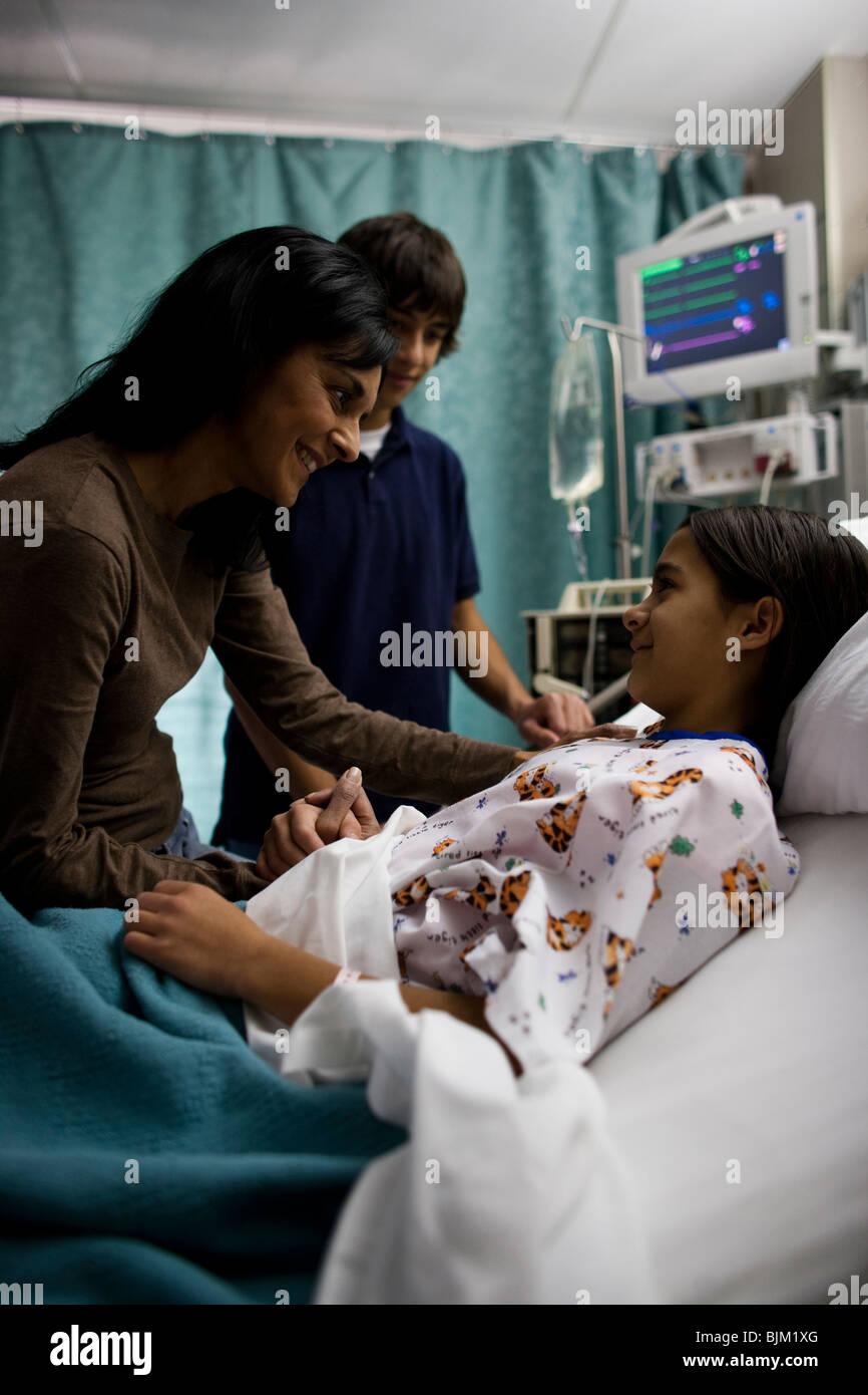 Familie sitzt mit Mädchen im Krankenhausbett Stockbild