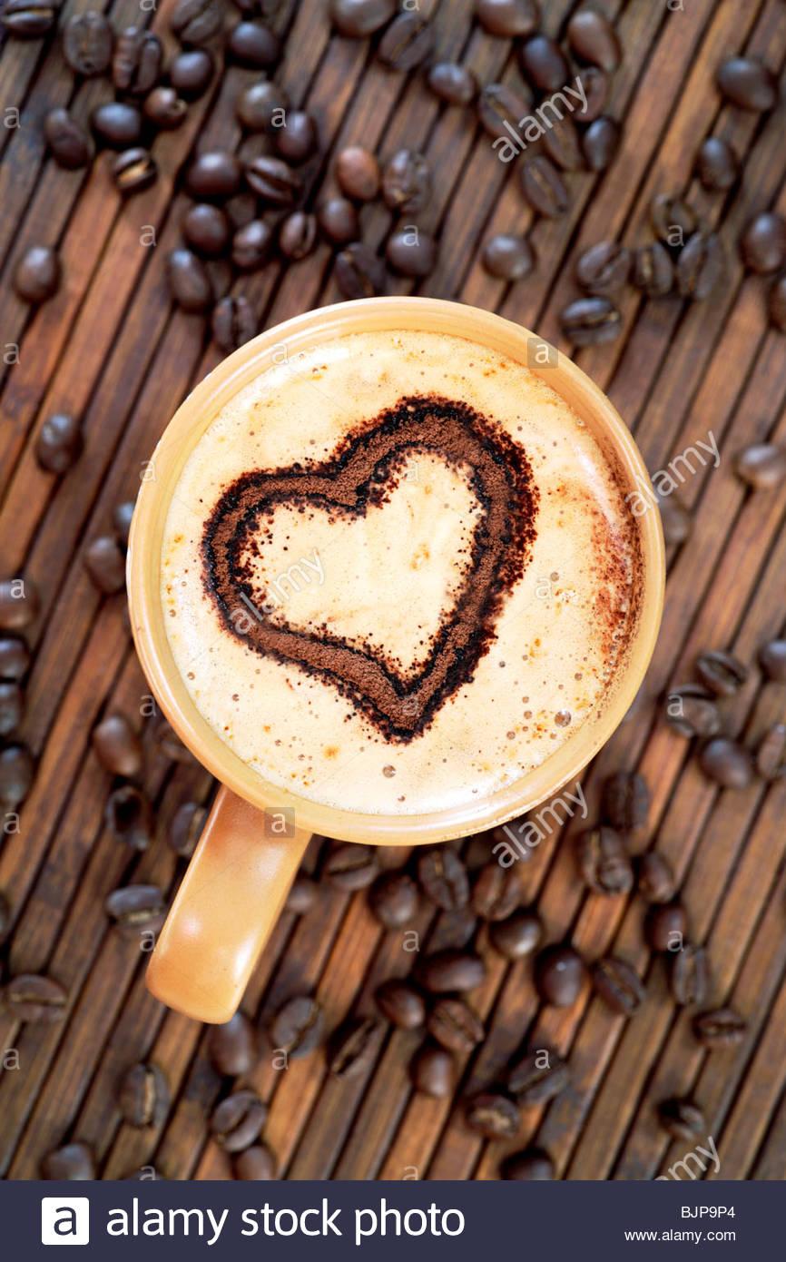 Cappuccino mit Herz Dekoration in Milchschaum & Kaffeebohnen Stockbild