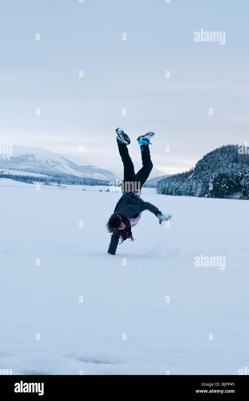 Junger Mann macht einen Handstand auf dem Eis der zugefrorenen See Pityoulish Stockbild