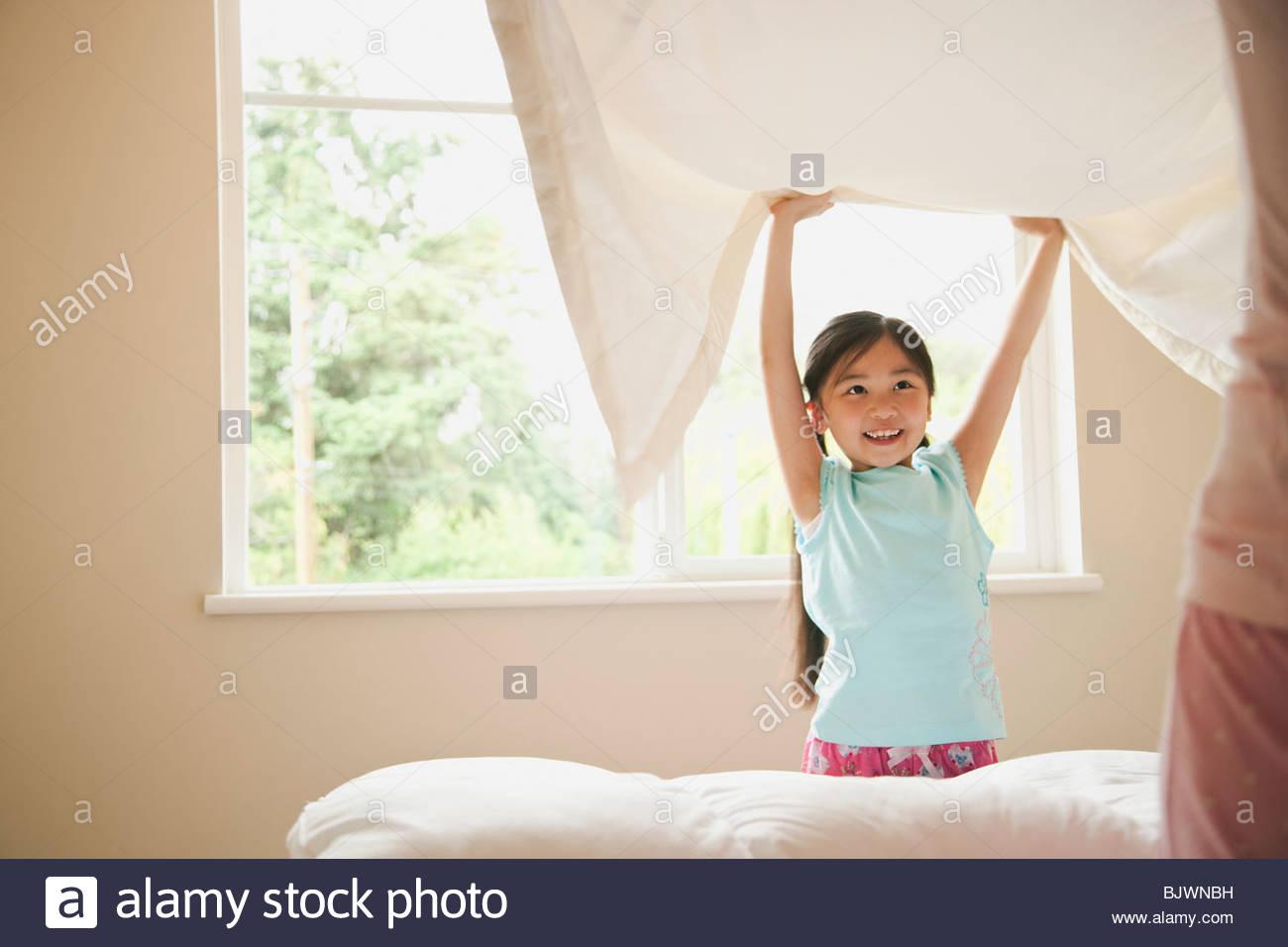 Mutter und Tochter das Bett machen Stockbild