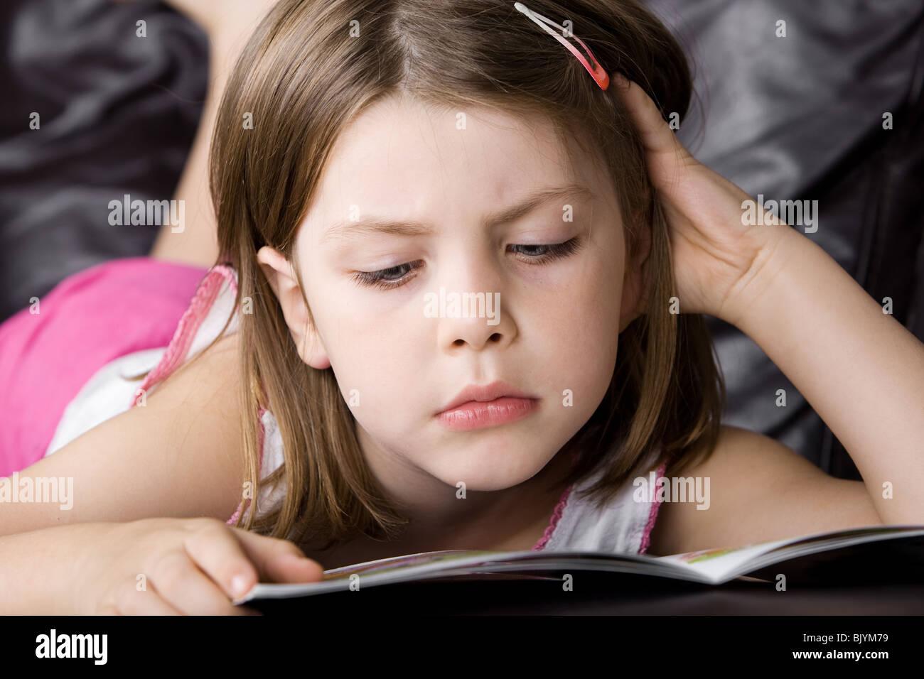 Schuss einen niedlichen jungen Kind lesen ihr Buch auf dem Sofa Stockbild