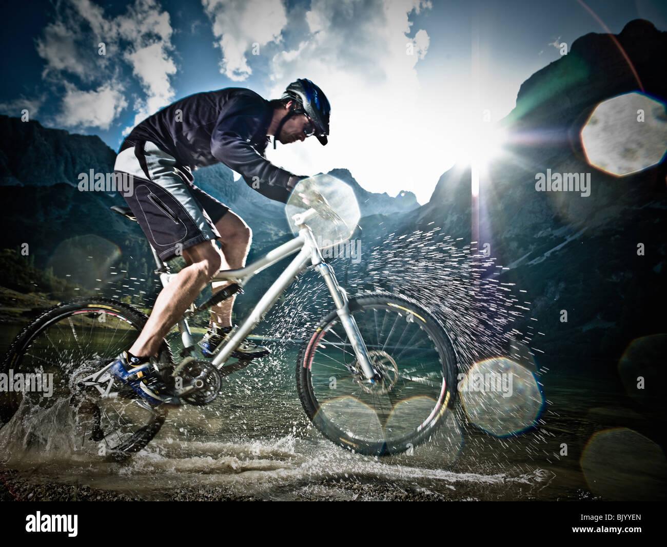 Männliche Mountainbiker fahren durch Wasser Stockbild