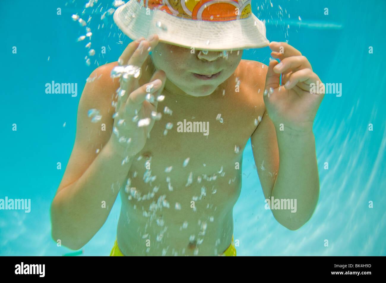 Junge mit angehaltenem Atem unter Wasser Stockbild