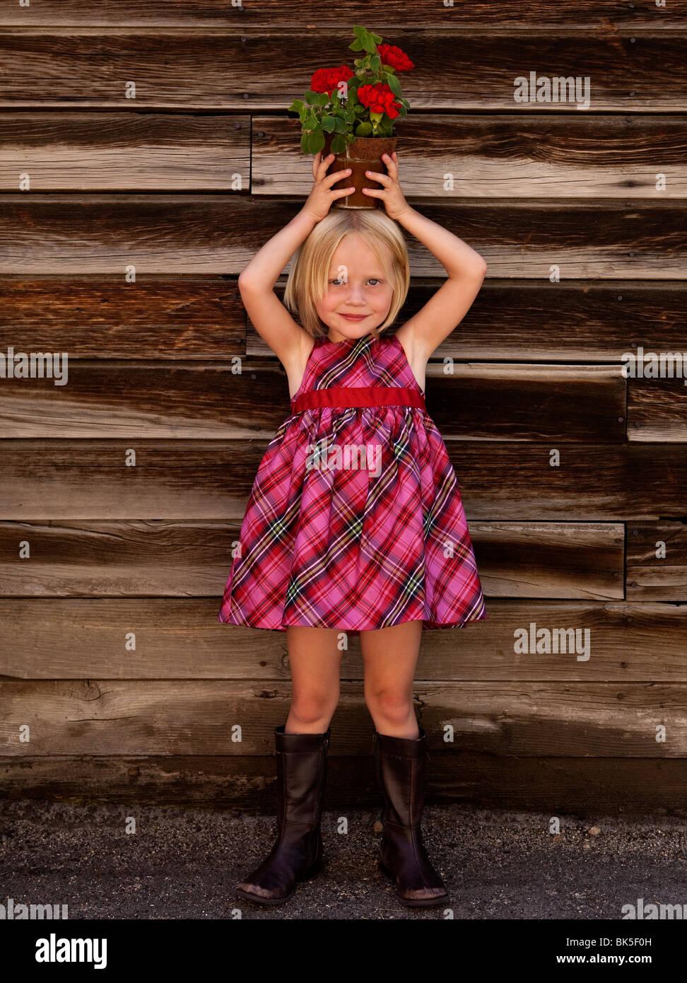 Kleines Mädchen in karierten Kleid mit Topfpflanze auf dem Kopf Stockbild