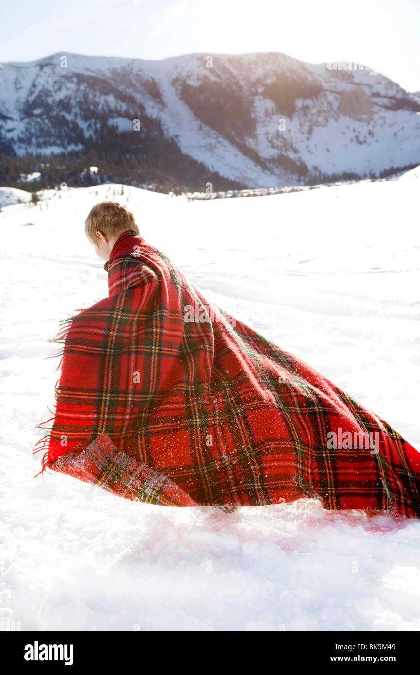 Kleiner Junge eingewickelt in rot karierte Decke im Schnee spielen Stockbild
