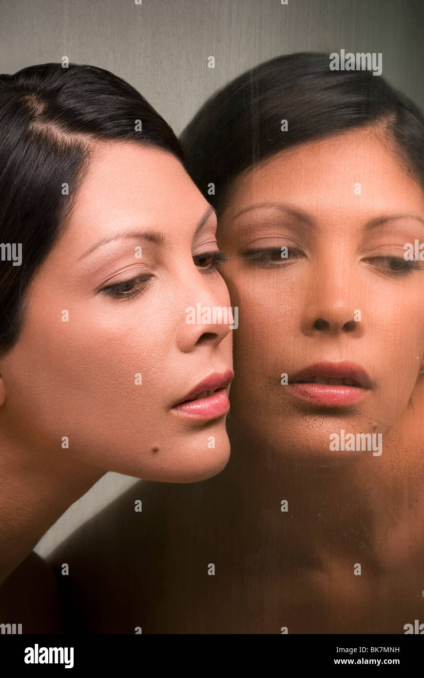 Junge Hispanic Frau und ihr Spiegelbild Stockfoto